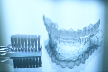 tooth brush placed next to set of clear aligners