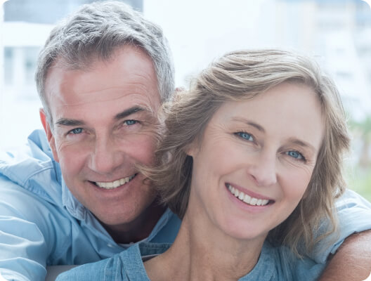 older man smiling and holding woman from behind