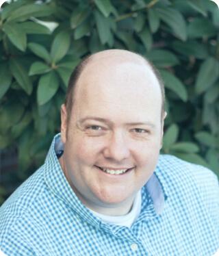 smiling bald man wearing blue plaid shirt outdoors