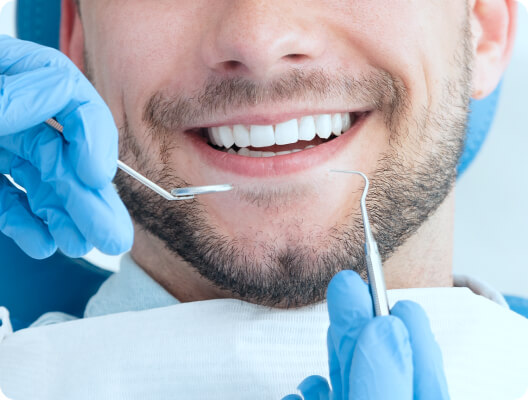 dentist using special tools on patient's smile