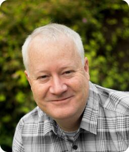 older man wearing grey plaid smiling outdoors