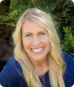 blonde smiling woman wearing blue shirt outdoors