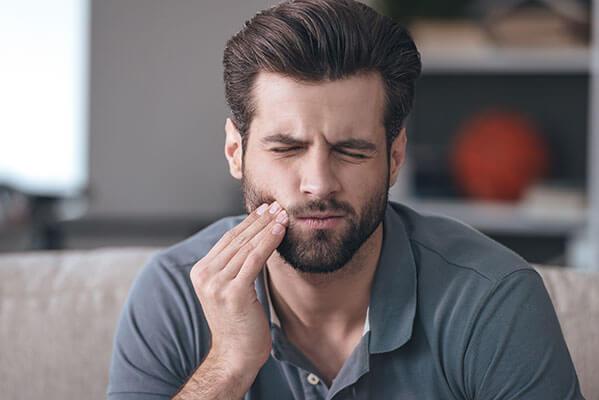 brunette man holding side of cheek in pain